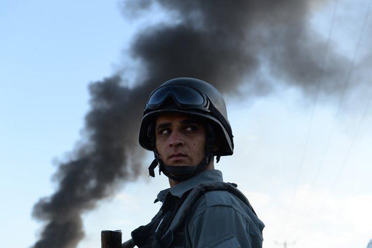 "An Afghan policeman guards the site of a suicide attack in Kabul on July 2, 2013. Pakistan could end the Afghan war ""in weeks"" if it were serious about peace, and is complicit in US drone strikes despite its denunciations of the anti-militant campaign, Afghanistan's army chief says"