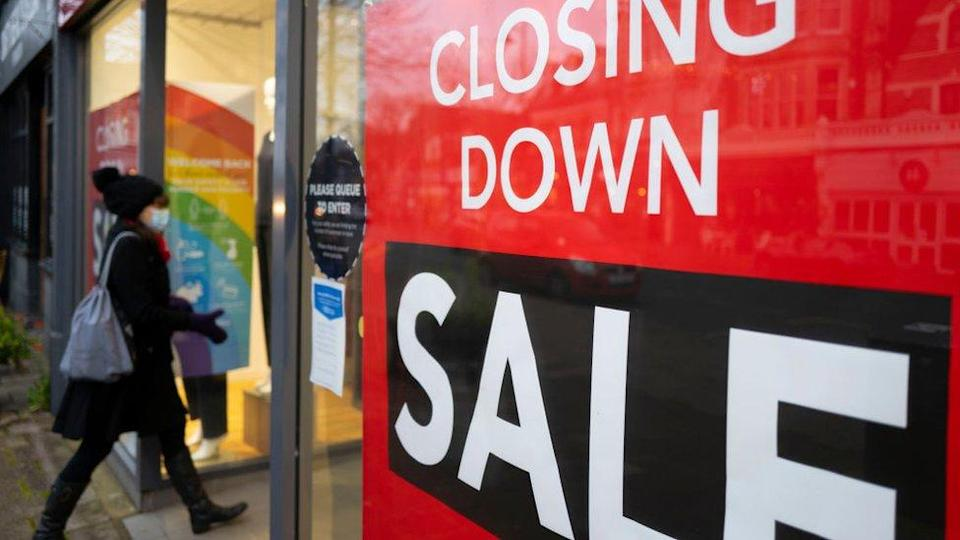 A woman walks into a shop with a closing down sale
