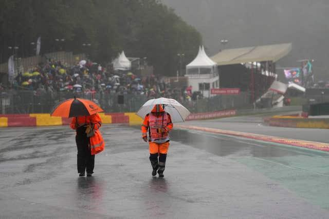 Stewards walk on the track during a rain delay at the Formula One Grand Prix at Spa-Francorchamps, where only two laps were eventually completed