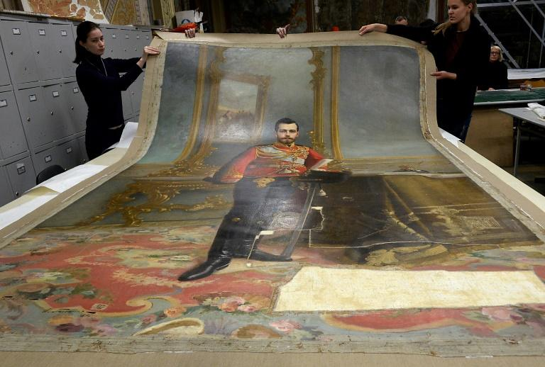Restorers at the Stieglitz Art and Industry Academy display the portrait of Russia's Tsar Nicholas II by Ilya Galkin (1896), in Saint Petersburg, in 2016