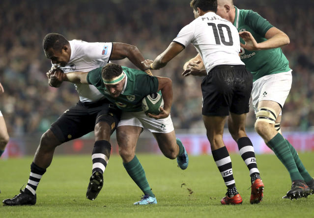 Ireland's Rob Herring is tackled by Fiji's Leone Nakarawa, left, during their International Rugby Union match at the Aviva Stadium, Dublin, Saturday, Nov. 18, 2017. (Brian Lawless/PA via AP)