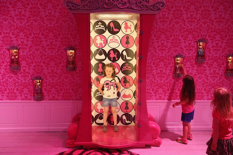 BERLIN, GERMANY - MAY 16:  Lara, 6, stands in a special armoire in Barbie's bedroom  while visiting the Barbie Dreamhouse Experience with her friends Josi and Luna on May 16, 2013 in Berlin, Germany. The Barbie Dreamhouse is a life-sized house full of Barbie fashion, furniture and accessories and will be open to the public until August 25 before it moves on to other cities in Europe.  (Photo by Sean Gallup/Getty Images)