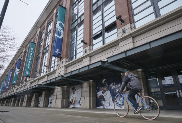 A bicyclist rides past T-Mobile Park, Wednesday, March 11, 2020, in Seattle, where baseball's Seattle Mariners plays home games. In efforts to slow the spread of the COVID-19 coronavirus, Washington State Gov. Jay Inslee announced a ban on large public gatherings in three counties in the metro Seattle area. That decision impacts the Seattle Mariners, Seattle Sounders, and the XFL's Seattle Dragons home games. (AP Photo/Stephen Brashear)