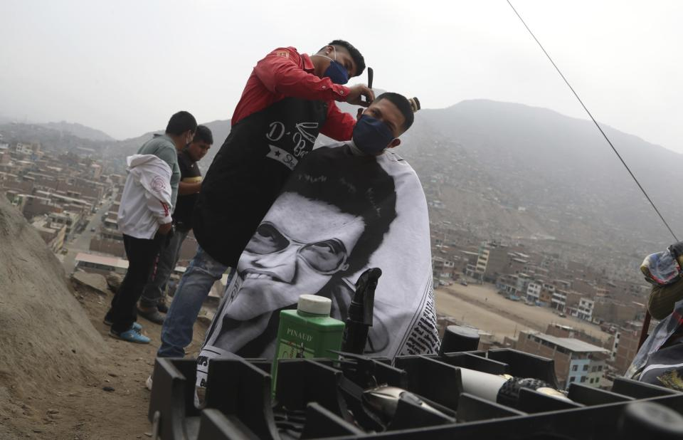 "Barber Josue Yacahuanca styles the hair of a resident free of charge at the top of a hill in the San Juan de Lurigancho neighborhood of Lima, Peru, Friday, June 19, 2020. ""I want them to look in the mirror and see a bit of hope,"" said Yacahuanca, who's just 21 years old but already considers himself a veteran barber because he starting cutting hair age 13. (AP Photo/Martin Mejia)"