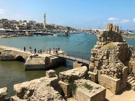 Tourists walk together at the sea castle in the port city of Sidon