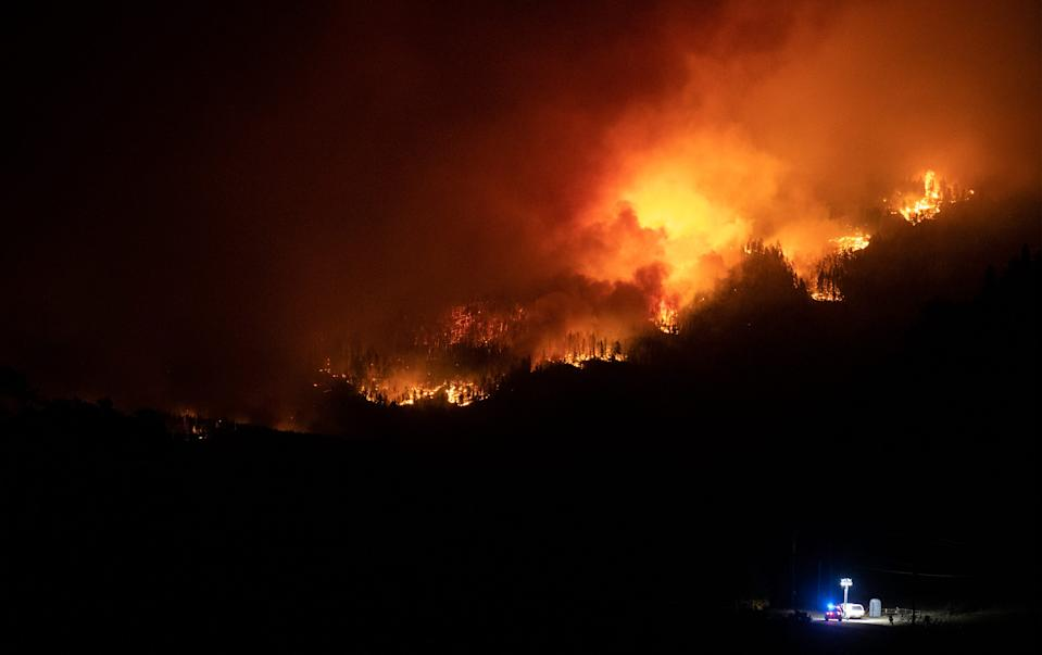 Flames work their way along a ridge near a road block as the Cameron Peak Fire burns outside Estes Park, Colo. on Friday, Oct. 16, 2020.