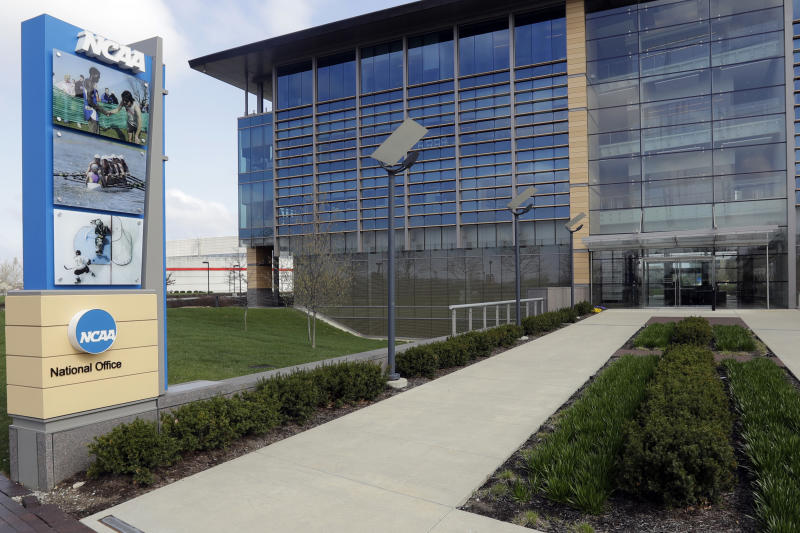 "FILE - This is an April 25, 2018, file photo, showing NCAA headquarters in Indianapolis. The NCAA Board of Governors took the first step Tuesday, Oct. 29, 2019, toward allowing athletes to cash in on their fame, voting unanimously to clear the way for the amateur athletes to ""benefit from the use of their name, image and likeness."" The United States' largest governing body for college athletics realized that it ""must embrace change to provide the best possible experience for college athletes,"" the board said in a news release issued after the vote at Emory University in Atlanta. (AP Photo/Darron Cummings, File)"