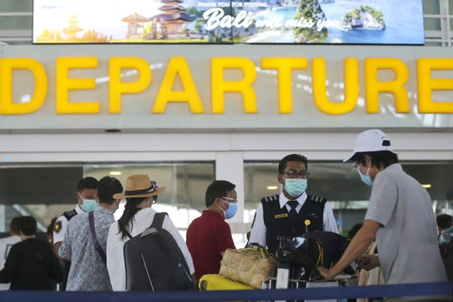 Tourists wearing face masks line up to a departure gate at Bali airport in Indonesia (Firdia Lisnawati/AP)