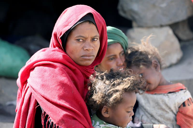 FILE PHOTO: Woman looks as she sits with her children at a camp for internally displaced people on the outskirts of Sanaa
