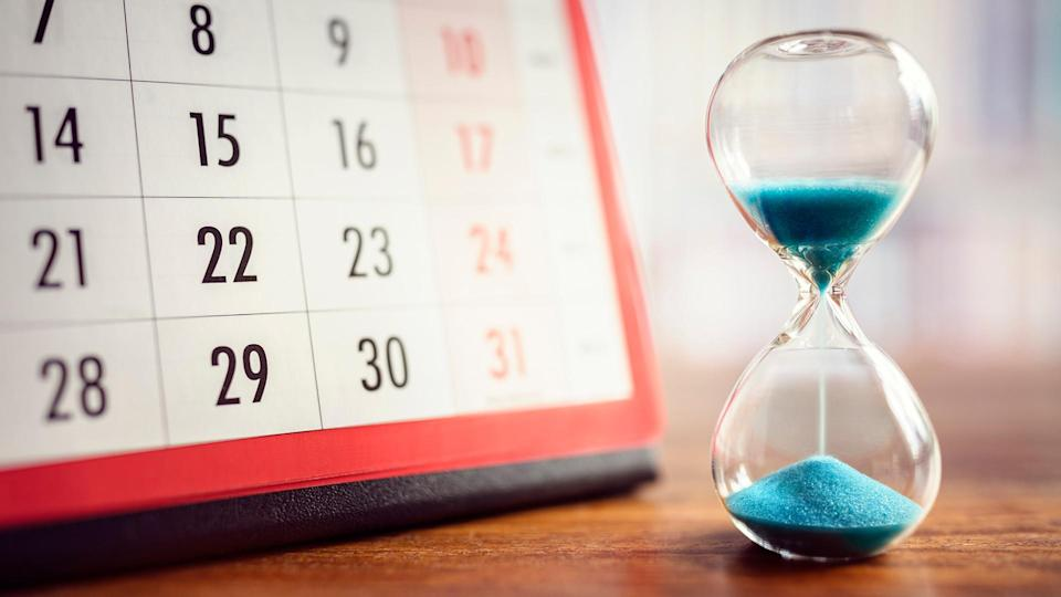 Hour glass and calendar concept for time slipping away for important appointment date, schedule and deadline.