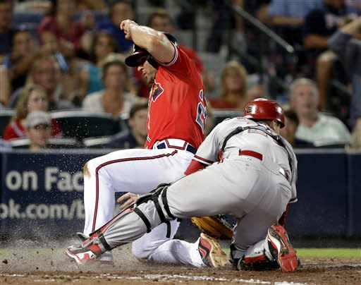 Atlanta Braves' Dan Uggla, left, scores past Arizona Diamondbacks catcher Miguel Montero off a bunt ground ball by Reed Johnson in the eighth inning of a baseball game, Friday, June 28, 2013, in Atlanta. The Braves beat the Diamondbacks 3-0. (AP Photo/David Goldman)