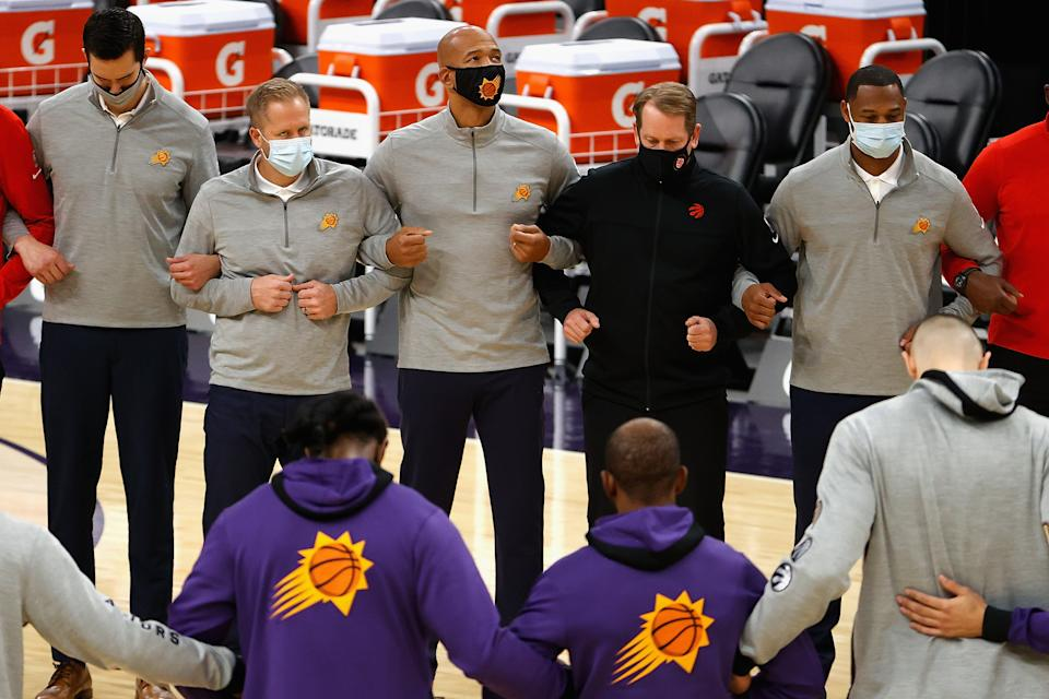 Phoenix Suns head coaches Monty Williams and Toronto Raptors head coach Nick Nurse stand arm-in-arm with their assistant coaches and players.
