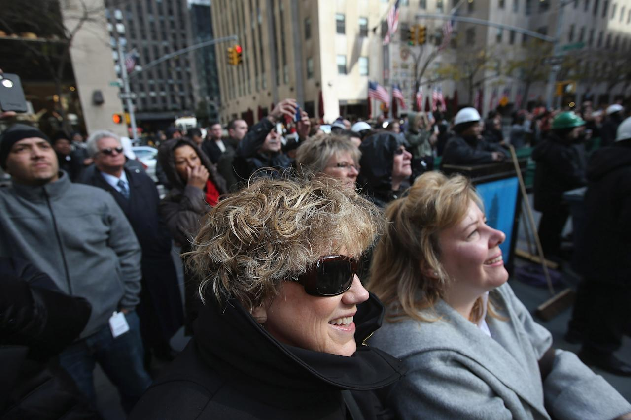 NEW YORK, NY - NOVEMBER 14:  People watch as the Rockefeller Center Christmas tree is about to be raised into position on November 14, 2012 in New York City. The tree, an 80-year old Norway Spruce, was donated by Joe Balku of Flanders, New Jersey. It weighs approximately 10 tons, measures 80 feet tall and is 50 feet in diameter. The official tree-lighting ceremony will be Wednesday, November 28.  (Photo by John Moore/Getty Images)