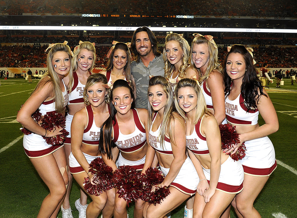 Jake Owen performs at halftime and poses with Florida State University Seminoles cheerleaders and players at the NCAA Discover Orange Bowl football game at the Sun Life Stadium in Miami, Florida.
