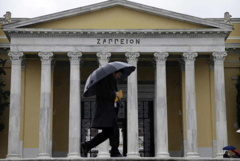 A pedestrian shields himself with an umbrella against driving rain as he walks past the neoclassical Corinthian colonnade in the portico of the Zappeion Hall, in central Athens, on Friday, Dec. 27, 2013. Rainstorms afflicted most of Greece Friday after clear skies on Christmas and Boxing Day. (AP Photo/Thanassis Stavrakis)