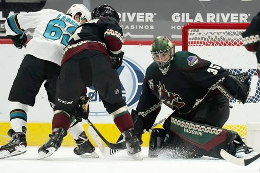 Arizona Coyotes goaltender Darcy Kuemper (35) goes after a puck on a shot from San Jose Sharks right wing Kevin Labanc, left, as Coyotes' Niklas Hjalmarsson (4) defends during the third period of an NHL hockey game Thursday, Jan. 14, 2021, in Glendale, Ariz. (AP Photo/Ross D. Franklin)
