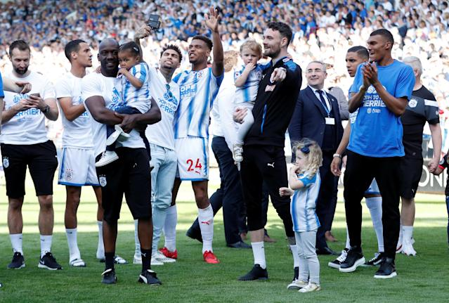 "Soccer Football - Premier League - Huddersfield Town vs Arsenal - John Smith's Stadium, Huddersfield, Britain - May 13, 2018 Huddersfield Town's Steve Mounie, Danny Williams and team mates celebrate in front of the fans at the end of the match Action Images via Reuters/Andrew Boyers EDITORIAL USE ONLY. No use with unauthorized audio, video, data, fixture lists, club/league logos or ""live"" services. Online in-match use limited to 75 images, no video emulation. No use in betting, games or single club/league/player publications. Please contact your account representative for further details."