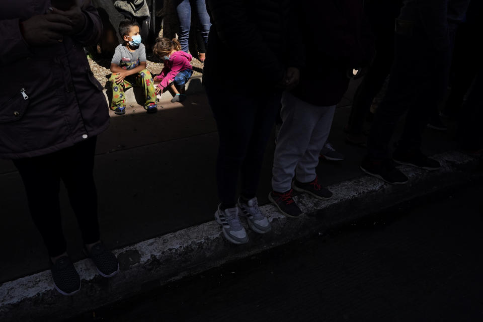 Two children play behind a row of migrants at a makeshift camp of migrants at the border port of entry leading to the United States, Wednesday, March 17, 2021, in Tijuana, Mexico. The migrant camp shows how confusion has undercut the message from U.S. President Joe Biden that it's not the time to come to the United States. Badly misinformed, some 1,500 migrants who set up tents across the border from San Diego harbor false hope that Biden will open entry briefly and without notice. (AP Photo/Gregory Bull)