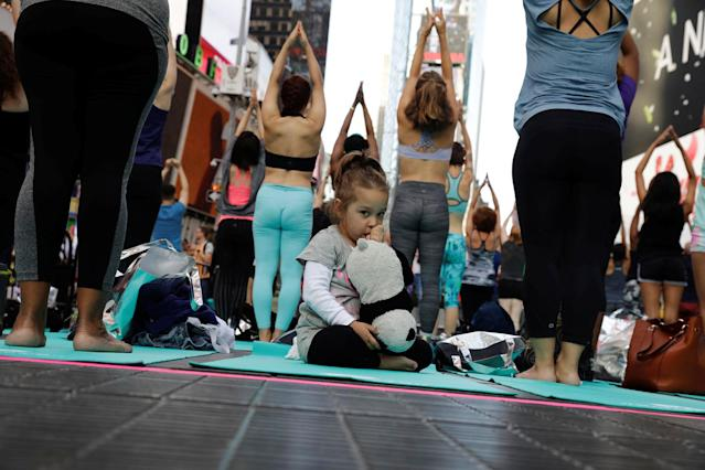 <p>A young girl sucks her thumb as people participate in a yoga class during an annual Solstice event in the Times Square district of New York, U.S., June 21, 2017. (Photo: Lucas Jackson/Reuters) </p>