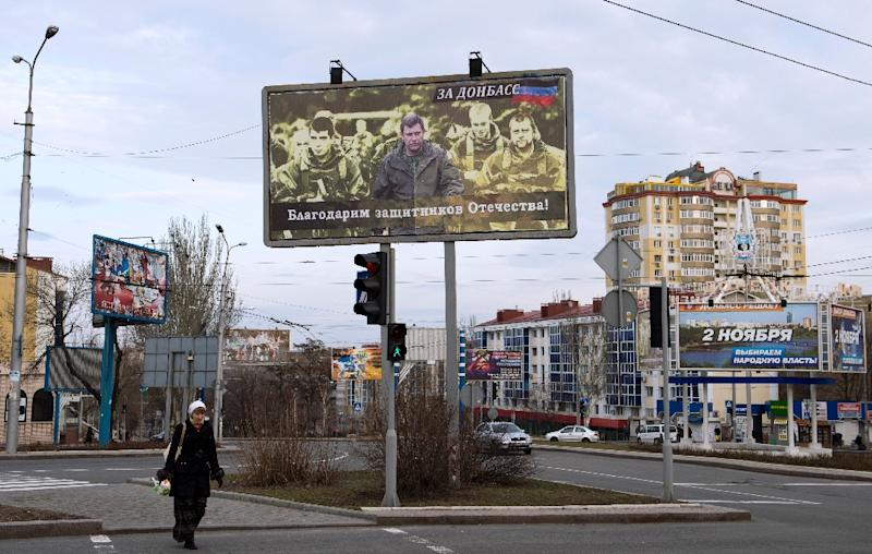 """A woman walks under a billboard featuring a picture of the leader of the self-proclaimed Donetsk People's Republic Alexander Zakharchenko (C) and reading: """"we are grateful to the defenders of the fatherland"""" in Donetsk, Ukraine, March 18, 2015"""