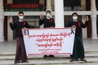 "Lawyers who graduated from the Yadanabon University flash the three-fingered salute of protest in Mandalay, Myanmar Saturday, Feb. 6, 2021. The military authorities in charge of Myanmar broadened a ban on social media following this week's coup, shutting access to Twitter and Instagram, while street protests continued to expand Saturday as people gathered again to show their opposition to the army takeover. A banner reads ""We condemn the unlawful coup. No to dictatorship."" (AP Photo)"