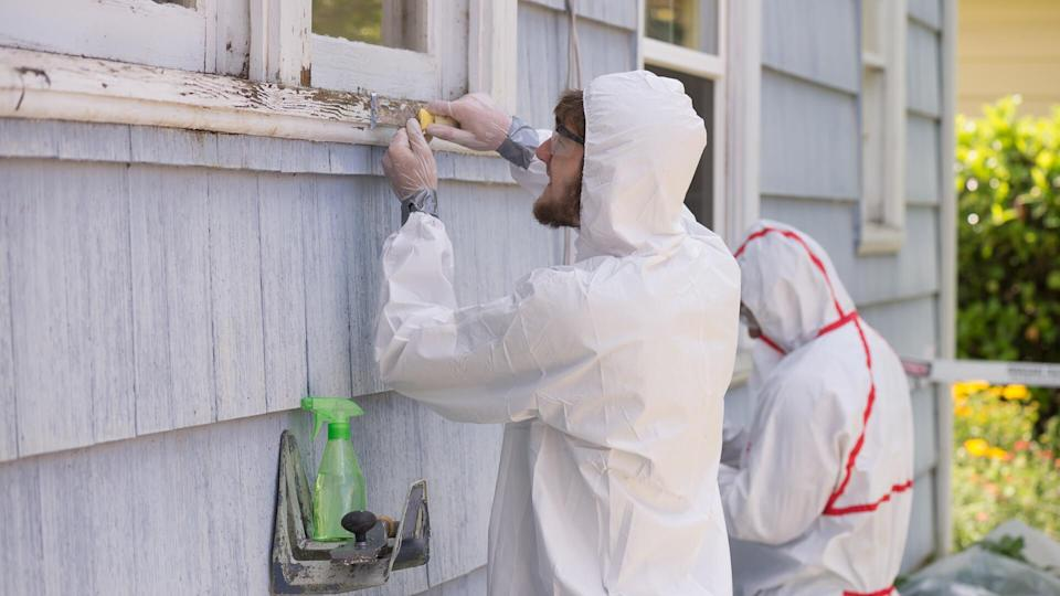 hazmat suit workers scrape off paint