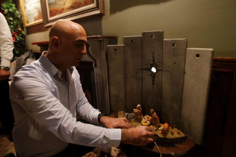 """Wisam Salsa, general manager of the Walled Off hotel, shows """"scar of Bethlehem"""" artwork by street artist Banksy, in Bethlehem in the Israeli-occupied West Bank"""