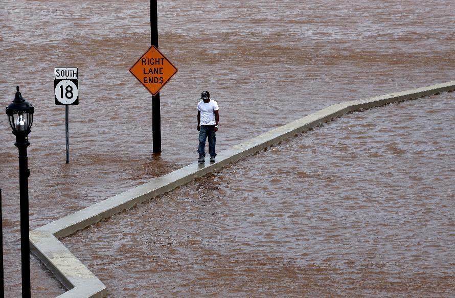 A man walks on top of a wall next to a flooded highway in New Brunswick, N.J., Aug. 28, 2011, as heavy rains left by Hurricane Irene are causing inland flooding of rivers and streams. Flood waters rose all across New Jersey on Sunday, closing roads from side streets to major highways as Hurricane Irene weakened and moved on, leaving 600,000 homes and businesses without power. (AP Photo/Mel Evans)