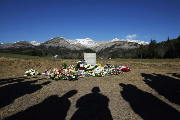 This file photo taken on April 6, 2015 shows people's shadows as they stand near a stela commemorating the victims of the March 24 Germanwings Airbus A320 crash in the village of Le Vernet, southeastern France, after a ceremony with victims' relatives
