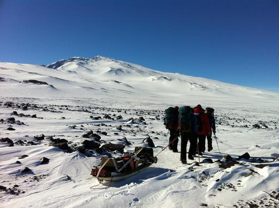 The POLENET/ANET field team drags equipment to install remote seismic and GPS stations at Mount Sidley, a volcano in Antarctica (seen in background).