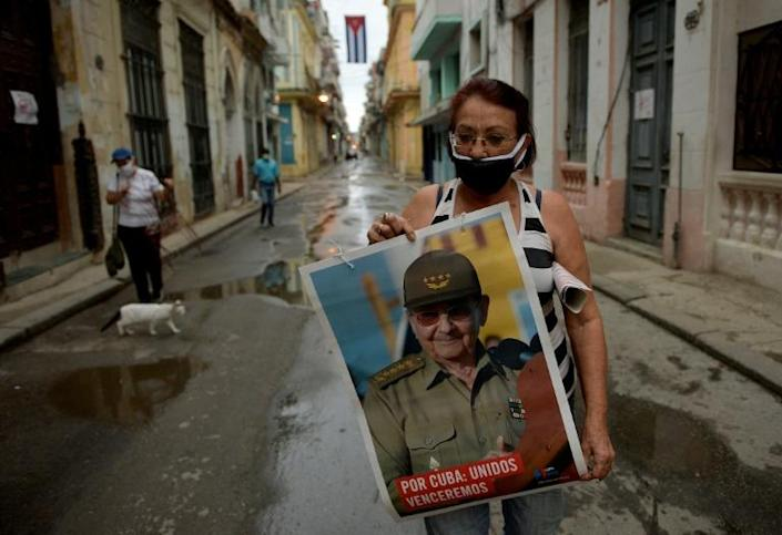 The head of the Committee for the Defense of the Revolution, Marta Parra, holding a poster of ex-president Raul Castro as she decorates her block to celebrate Workers' Day in Havana (AFP Photo/YAMIL LAGE)