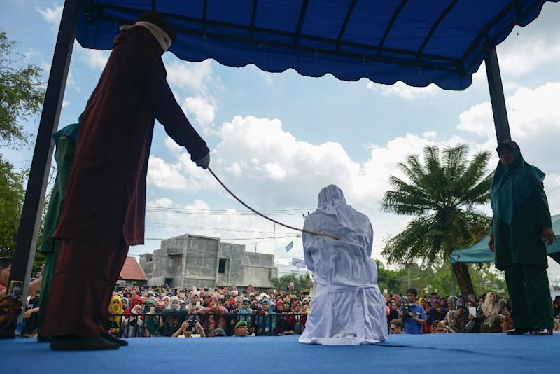 More than a thousand people, including dozens of tourists from neighbouring Malaysia, jeered and screamed abuse at the group as they were flogged outside a mosque in the capital Banda Aceh (AFP Photo/CHAIDEER MAHYUDDIN)
