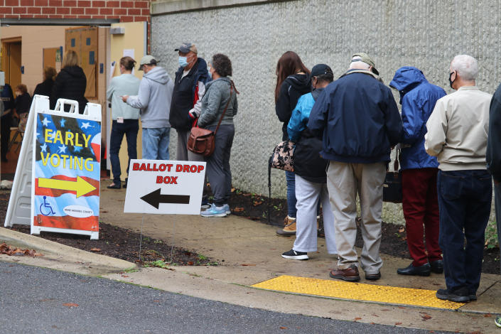 FILE - In this Monday, Oct. 26, 2020, file photo, voters wait in line to enter the Pip Moyer Recreation Center, in Annapolis, Md., on the first day of in-person early voting in the state. Tens of millions of Americans already cast ballots in the 2020 election amid record-breaking early voting during the coronavirus pandemic. But for some voters in a handful of states, casting an early ballot in-person isn't even an option. (AP Photo/Brian Witte, File)