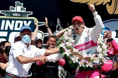 Frédéric Lissalde shakes the hand of Helio Castroneves as he celebrates his fourth Indianapolis 500 win in Victory Circle at Indianapolis Motor Speedway