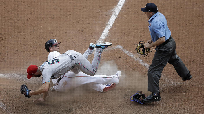 Atlanta Braves' Austin Riley, center, slides into home plate as Miami Marlins' Anthony Bass, left, topples over him during the 10th inning of a baseball game Sunday, July 4, 2021, in Atlanta. After a review of the play, the ruling on the field was overturned and Riley was called out. (AP Photo/Ben Margot)