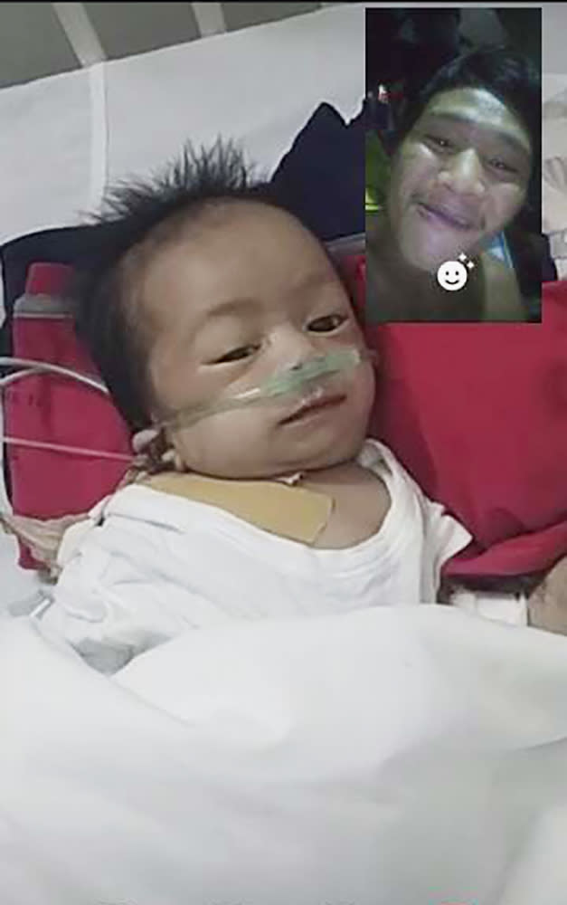 This photo provided by Ronnel Manjares shows Kobe Christ Manjares during a video call with him, upper right, at a hospital in metropolitan Manila, Philippines, Tuesday, June 2, 2020. Manjares' 16-day-old son Kobe was heralded as the country's youngest COVID-19 survivor. But the relief and joy proved didn't last. Three days later, Kobe died on June 4 from complications of Hirschsprung disease, a rare birth defect. (Ronnel Manjares via AP)
