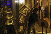 A waiter carries chairs to close a bar terrace in Paris, Monday Sept. 28, 2020. French President Emmanuel Macron justified on Monday new restrictions in the country to limit the spread of the virus as restaurant and bar owners forced to shut down expressed anger at the measures. Milder restrictions have been ordered in ten other cities including Paris, with gyms shut down, public gatherings of more than 10 people banned and bars ordered to close at 10 p.m. (AP Photo/Francois Mori)