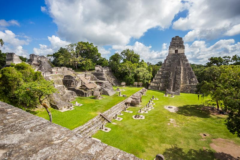 View of majestic mayan ruins with green grass and trees at Tikal National Park in Guatemala near the border of Belize.