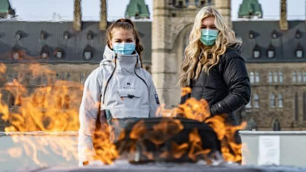 Two women wearing masks stare at the Centennial Flame on Parliament Hill in Ottawa on Feb. 18. The city enters red-zone territory on the pandemic scale at 12:01 a.m. ET Friday. (Brian Morris/CBC - image credit)