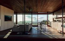 The main house and its porch were shipped nearly complete and each element was cantilevered onto the site. Sliding glass walls provide access to sweeping views of the landscape.