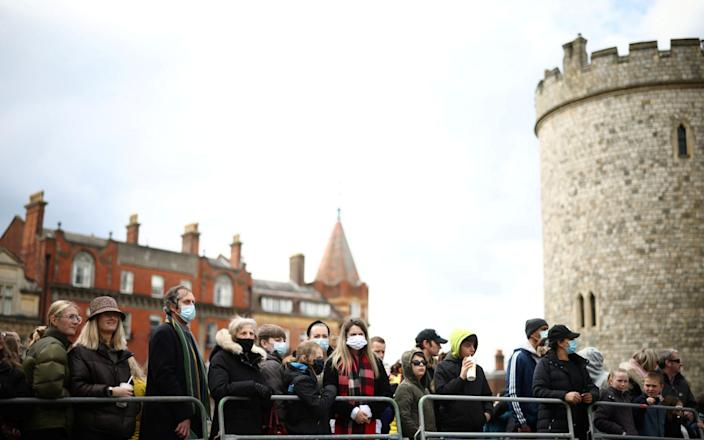Mourners gather outside the castle in defiance of requests not to do so