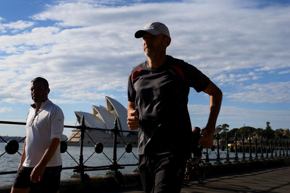 People are seen exercising in the early morning in Sydney, Australia.