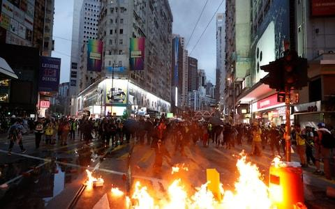 Some protesters lit fires to block traffic in the city centre - Credit: Vincent Thian/AP
