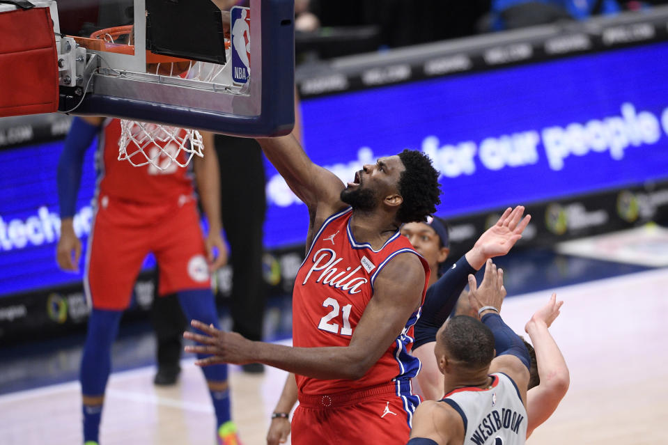 Philadelphia 76ers center Joel Embiid (21) dunks past Washington Wizards guard Russell Westbrook, bottom, during the second half of an NBA basketball game Friday, March 12, 2021, in Washington. (AP Photo/Nick Wass)