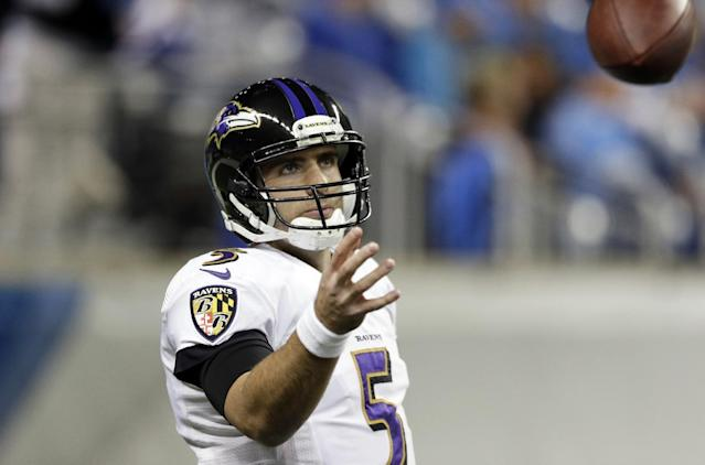 Baltimore Ravens quarterback Joe Flacco reaches for the football during warm ups before an NFL football game against the Detroit Lions in Detroit, Monday, Dec. 16, 2013. (AP Photo/Carlos Osorio)
