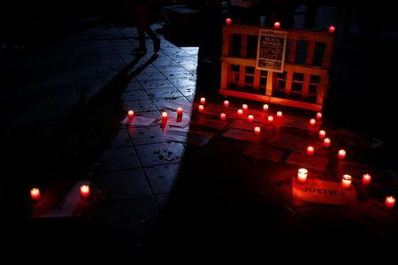 Candles and posters are seen on the ground during a silent candlelight vigil to protest against the assassination of investigative journalist Daphne Caruana Galizia in a car bomb attack two days ago, at the University of Malta in Msida, Malta, October 18, 2017.  REUTERS/Darrin Zammit Lupi