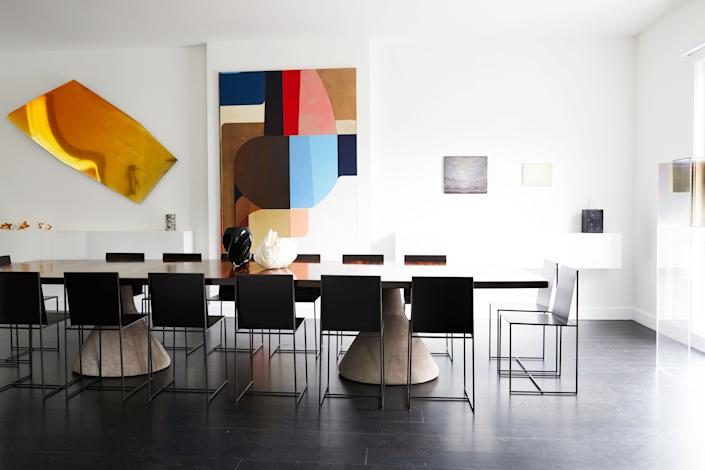"<div class=""caption""> The gallery-like dining room features a series of striking contemporary artworks, including an untitled multicolored oil on canvas by Svenja Deininger, and a golden wall sculpture by Nicola Martini (made of wax and bithumen on plexiglas). A table from the 1960s, designed by Jorge Zalszupin with a jacarandá top and sturdy concrete bases covered in suede, quietly anchors the space. The minimalist metal chairs, called Slim Sissi, were designed by <a href=""https://www.zeusnoto.com/portfolio/slimsissi/"" rel=""nofollow noopener"" target=""_blank"" data-ylk=""slk:Maurizio Peregalli for Zeus Noto"" class=""link rapid-noclick-resp"">Maurizio Peregalli for Zeus Noto</a>. </div>"