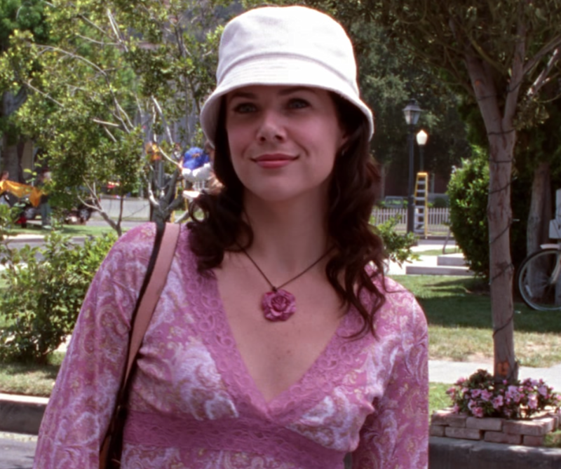 Okay, I'll give Lorelai retroactive points for the bucket hat, which has seen a resurgence of late, but there's simply no excuse for the tacky rose pendant and straight-from-Delias lacy pink shirt she's wearing.
