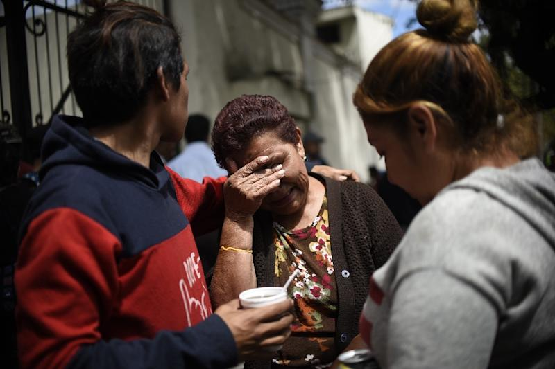 Relatives of the victims of a fire at a government-run children's shelter in San Jose Pinula, cry outside the morgue in Guatemala City