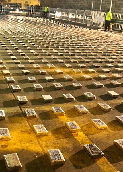 Police officers guard packages of cocaine seized in Cartagena, Colombia, on January 13, 2015 (AFP Photo/Policia Nacional De Colombia, Policia Nacional De Colombia)